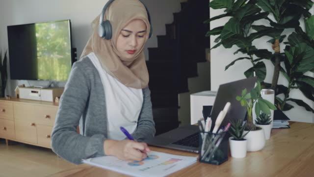 vídeos de stock e filmes b-roll de muslim woman working on laptop computer in living room at home - oriente médio