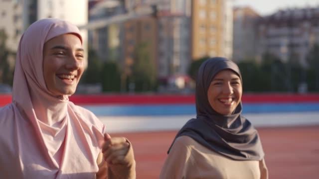 vidéos et rushes de femmes musulmanes faisant du jogging sur la piste de course - vêtement religieux