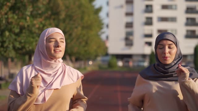 muslim women jogging on the running track - hijab stock videos & royalty-free footage