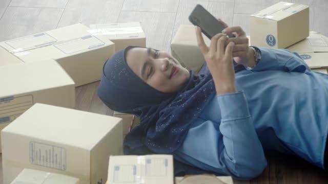 vidéos et rushes de les femmes musulmanes se détendre, vérifier le montant des commandes sur smartphone. - vêtement religieux