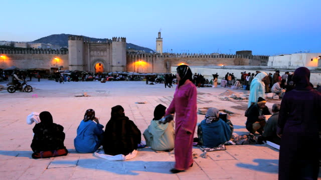 muslim women sit outside the kasba city gate. - burka stock videos and b-roll footage