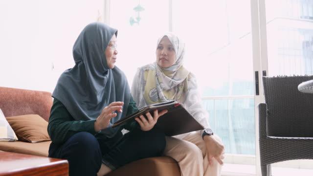 vídeos de stock, filmes e b-roll de mulheres muçulmanas usando um computador tablet juntos - vestuário modesto