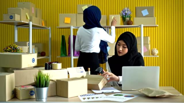 vidéos et rushes de femmes musulmanes travaillant en utilisant un ordinateur portable faisant la vente en ligne dans l'internet au bureau moderne coloré - malaysian culture