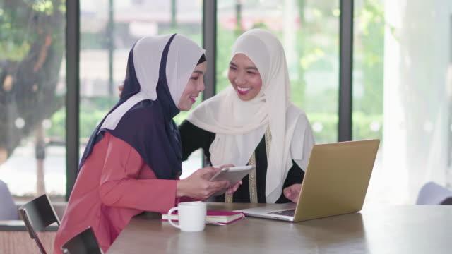 イスラム教徒の女性は、共同の作業スペースにタブレットとノート パソコンを操作します。 - モロッコ文化点の映像素材/bロール