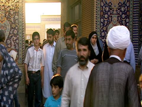 vidéos et rushes de muslim worshipers entering and departing through arched doorway at qom shrine / qom, iran - format vignette
