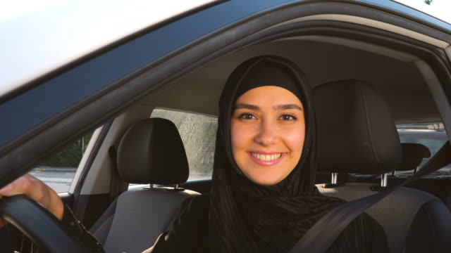 muslim young woman looking at camera in car - front view stock videos & royalty-free footage
