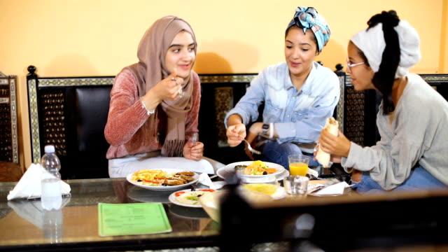 muslim young women having a lunch break together in an arab restaurant - religioni e filosofie video stock e b–roll