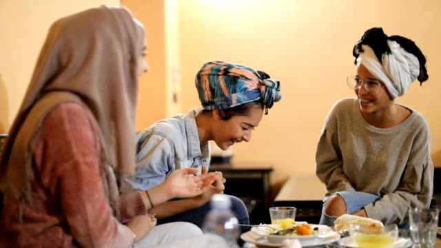 vídeos de stock e filmes b-roll de muslim young women having a lunch break together in an arab restaurant - lenço na cabeça enfeites para a cabeça