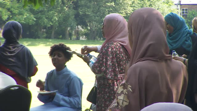 """muslims celebrating eid together in park in south london after all coronavirus restrictions were lifted - """"bbc news"""" stock videos & royalty-free footage"""