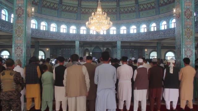 muslims perform eid prayer at blue mosque on the first day of the muslim festival of eid aladha on august 21 2018 in mazarisharif afghanistan - アフガニスタン点の映像素材/bロール