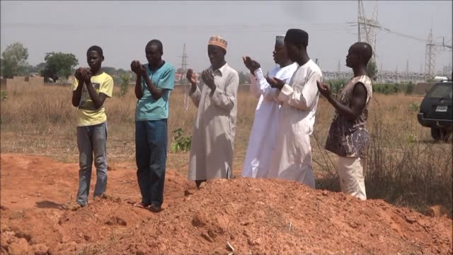 muslims pray at the site where public officials and human rights group amnesty international say the bodies of some 350 shiite muslims including... - shi'ite islam stock videos & royalty-free footage