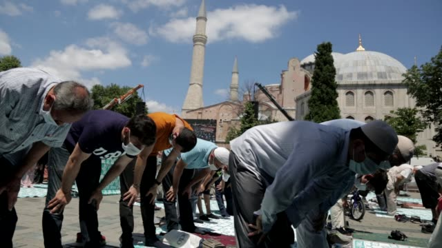 vídeos de stock e filmes b-roll de muslims pray the noon prayer outside the hagia sophia mosque on july 25 2020 in istanbul turkey on the second day the hagia sophia mosque was opened... - meio dia