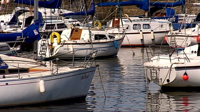 musselburgh ext people walking along the beach / small boats lined up on beach / sailing boats anchored in harbour / boat leaving harbour / buildings... - anchored stock videos & royalty-free footage