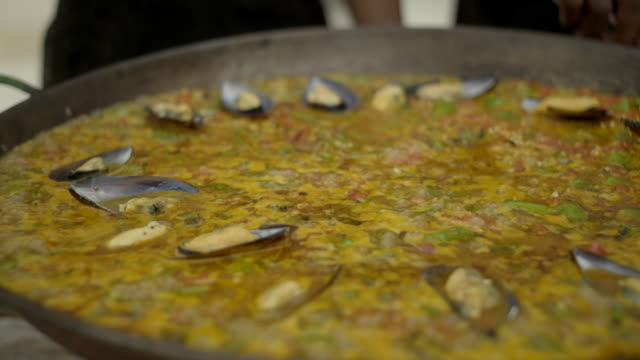 mussels are added to a bubbling pan of paella - market stall stock videos & royalty-free footage