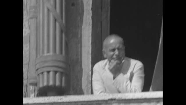vídeos y material grabado en eventos de stock de mussolini standing on balcony talking out and turning to inside and talking, can see part of fasces to his right; he rests elbow on balustrade / same... - mussolini