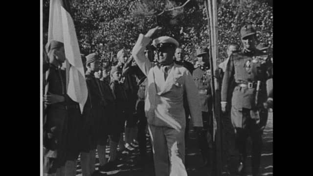stockvideo's en b-roll-footage met mussolini walks past line of soldiers and gives an exaggerated salute / he poses with a soldier and two civilians - benito mussolini