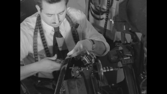 Mustachioed editor with loops of developed film around his neck looking through a Moviola viewfinder