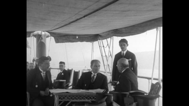 Mustafa Kemal Ataturk on a boat with dignitaries and a photographer / A motor launch on the Bosporus passing large crowds / Mustafa waves...