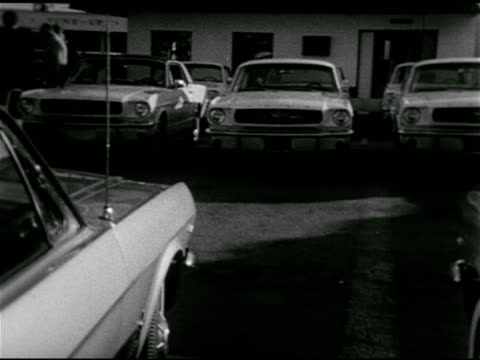 stockvideo's en b-roll-footage met mustang logo on steering wheel zo ms reverse pan ford dealership lot filled w/ mustang's sports cars for sale ms behind adult male w/ younger female... - 1964