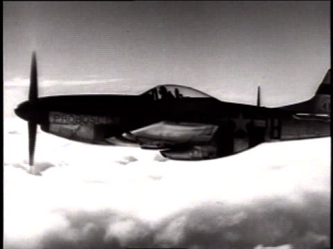 Mustang P51 fighter plane flying in sky then banking a turn above the clouds / United States