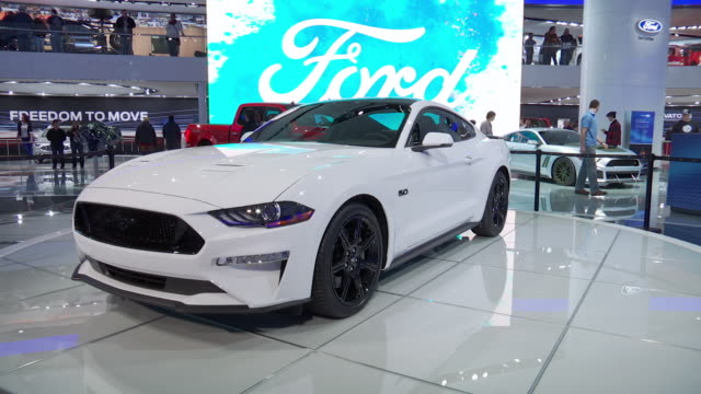 ws mustang revolving on turntable / ws ford design manager melvin bentancourt posing for pictures beside front end of mustang / cu front end of... - ford mustang stock videos and b-roll footage