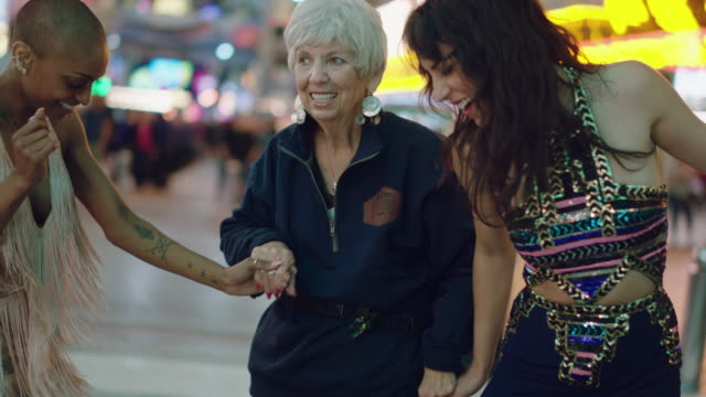 muti-ethnic lesbian newlyweds dance with an elderly woman on fremont st. in las vegas - social issues stock videos & royalty-free footage