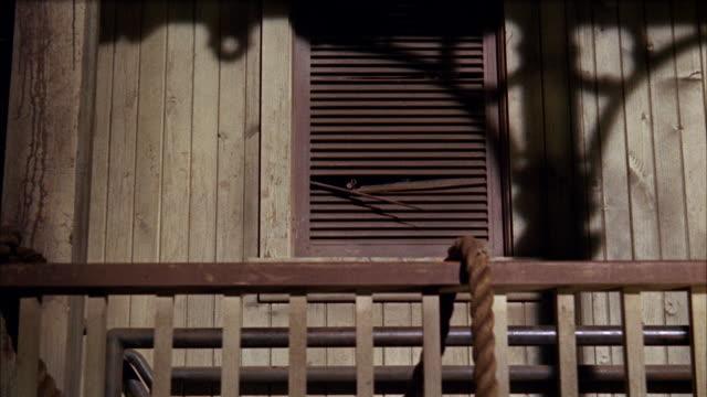 MS Muzzle of double barrel shotgun protruding through door slats