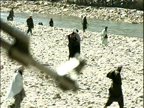 vidéos et rushes de muzzle of rifle being held by northern alliance soldier watching over pashtun prisonersofwar war in afghanistan 2001 - guerre d'afghanistan : de 2001 à nos jours