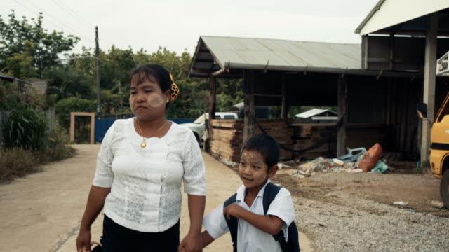 vidéos et rushes de m/s steadycam myanmar boy and mother going to the school bus - cartable