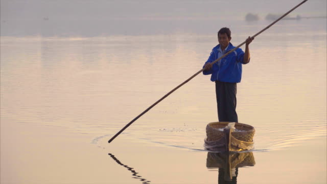vidéos et rushes de myanmar local man rowing boat toward camera - industrie de la pêche