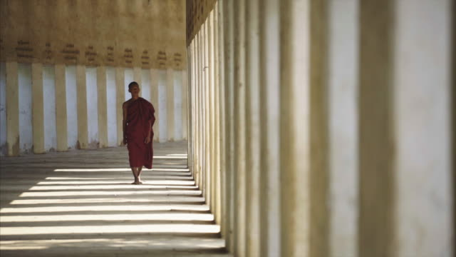myanmar monk walking to the camera in shade light hall - one teenage boy only stock videos & royalty-free footage