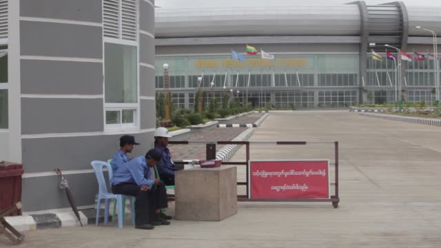 a myanmar police force officer directs a vehicle arriving at the myanmar international convention center ahead of the world economic forum on east... - 警備員点の映像素材/bロール