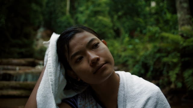 M/S SLO MO Myanmar teenage girl drying her hair after a bath in a waterfall in the forest