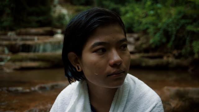 vídeos y material grabado en eventos de stock de m/s slo mo myanmar teenage girl drying herself after a bath in a waterfall in the forest - sólo una adolescente