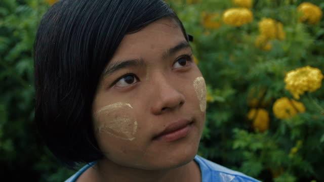 vídeos y material grabado en eventos de stock de c/u slo mo myanmar teenage girl in a field of yellow mums, rain - sólo una adolescente