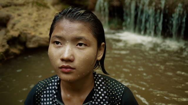 stockvideo's en b-roll-footage met m/s slo mo myanmar teenage girl taking a bath in a waterfall in the forest - alleen één tienermeisje