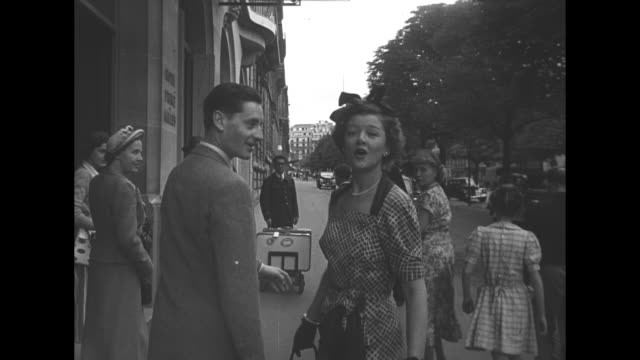 MS Myrna Loy actress walks down street with unid man seen from behind / MS Loy turns to face camera smiles and waves then turns and walks off