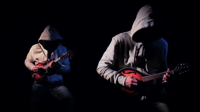 mysterious anonymous musicians in hoodies playing mandolin - chiaroscuro stock videos and b-roll footage