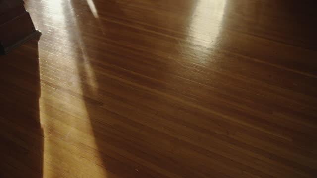 a mysterious human shadow crosses a vintage oak wooden floor. - 床点の映像素材/bロール
