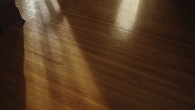 a mysterious human shadow crosses a vintage oak wooden floor. - wood grain stock videos & royalty-free footage