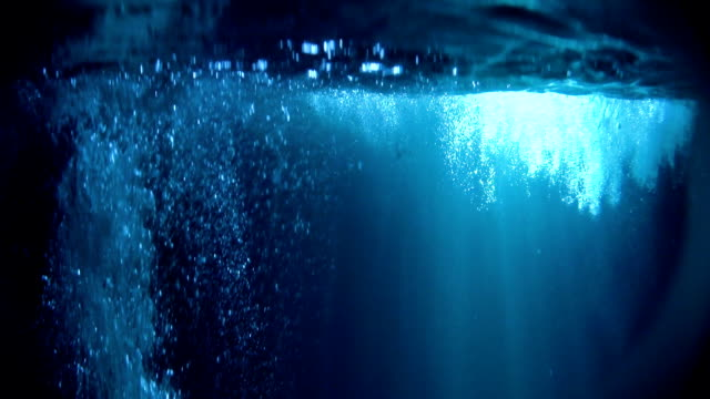 Mysterious underwater scenery with bubbles. Bright object in background