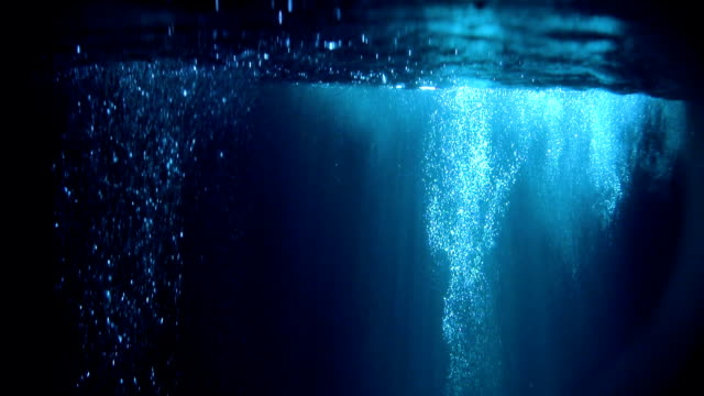 vídeos de stock e filmes b-roll de mysterious underwater scenery with glowing bubbles - escuro
