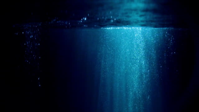 mysterious underwater scenery with glowing bubbles - deep stock videos & royalty-free footage