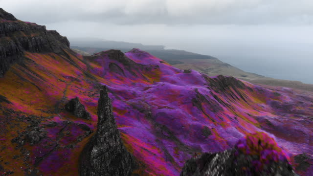 vídeos de stock e filmes b-roll de mystical footage flying with drone above dramatic landscape with infrared colors in scotland. - pináculo formação rochosa