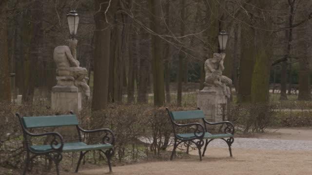 vídeos de stock e filmes b-roll de mythical faun figurines clutch lampposts in łazienki park, warsaw, poland. - banco assento