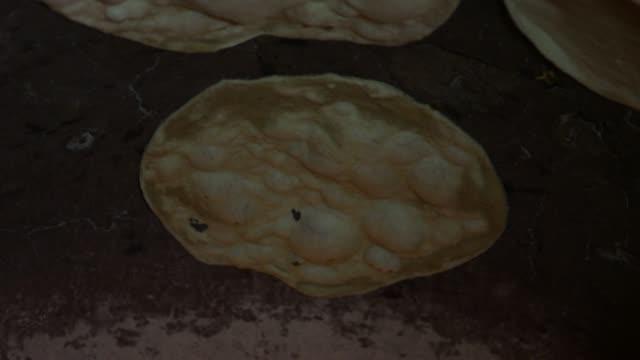 a naan bread being baked and rising in the oven in punjab, pakistan - punjab pakistan bildbanksvideor och videomaterial från bakom kulisserna
