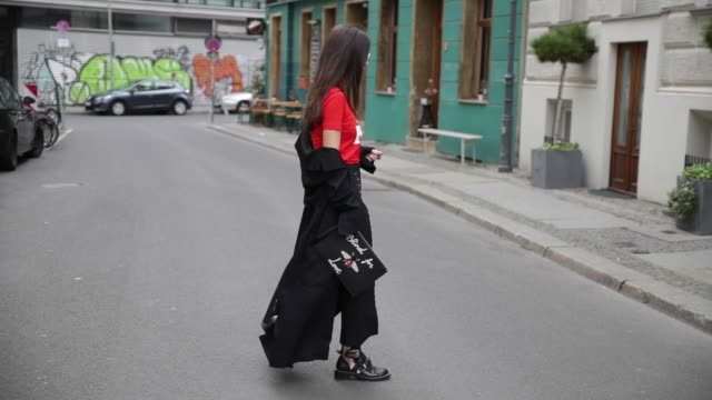 Nadja Ali wearing a black Lala Berlin coat a red Ganni tshirt with the print Cherry bomb black Zara pants Gucci clutch with the print blind for love...