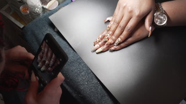 A nail artist taking a picture of her work on a clients hands in a nail studio.