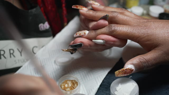 a nail artist working on a clients hands in a nail studio. - beauty spa stock videos & royalty-free footage