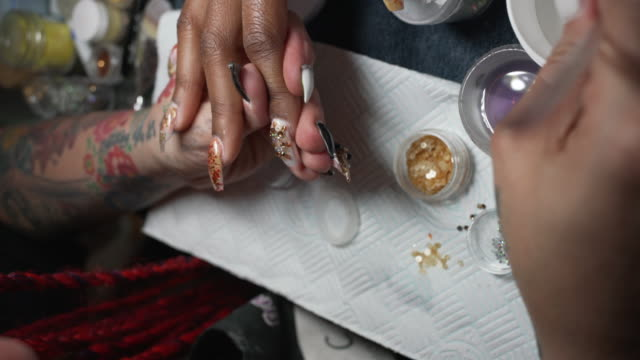 a nail artist working on a clients hands in a nail studio. - manicure stock videos & royalty-free footage